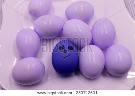 Group Of Colorful Painted Easter Eggs With Funny Cartoon Style Faces In A Light Blue Egg Box On Purp
