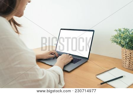 Young Asian Woman Working Using And Typing On Laptop With Mock Up Blank White Screen While At Home I