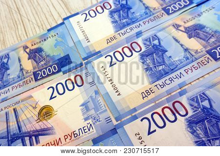 Man's Hand Holds A New Russian Banknote Of Two Thousand Rubles Against The Background Of Green Cash