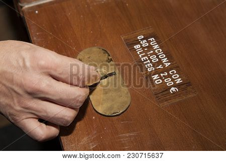 Hand Of A White Man Inserting A Euro Coin In To The Slot Where To Insert Coins On Varnished Wood
