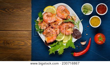 Prawns Shrimps Roasted With Garlic And Rosemary, Served On Plate With Mizuna Lettuce, Lemon And Set