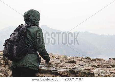 Young Girl In A Green Jacket With A Backpack Looking At The Landscape And Forest In The Fog