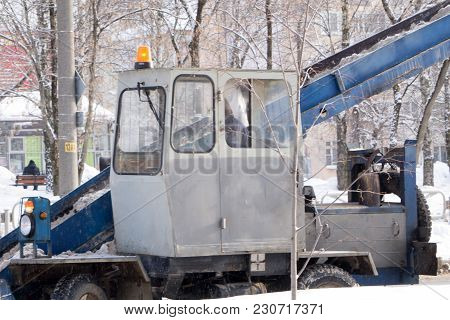 Tractor Cleaning The Road From The Snow. Excavator Cleans The Streets Of Large Amounts Of Snow In Ci