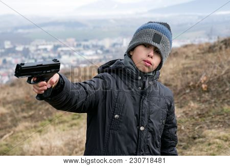 Young Boy With Angry Face And Gun
