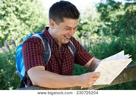 Man Hiking In Countryside Looking At Map
