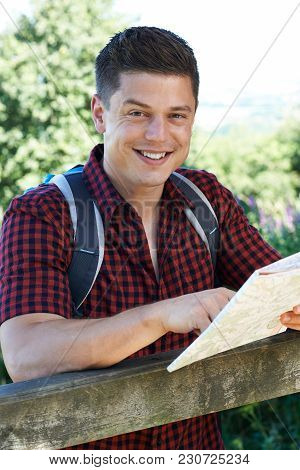Portrait Of Man Hiking In Countryside With Map