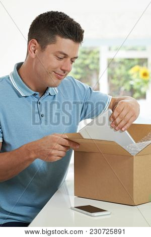 Man At Home Unwrapping Digital Tablet Bought Online