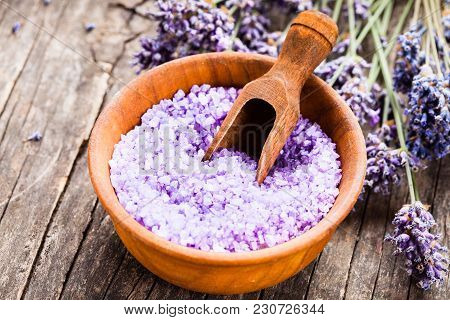 Scoop With Lavender Seasalt In Wooden Bowl. Spa Lavender Treatment Concept