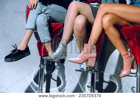 Low Section Of Fashionable Girls Sitting On Bar Stools