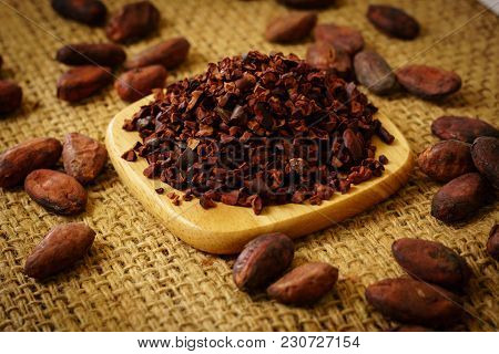 Cacao Nibs And Cocoa Beans On Burlap Background