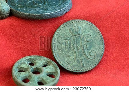 A Copper Old Russian Coin And A Round Wheel On A Red Background
