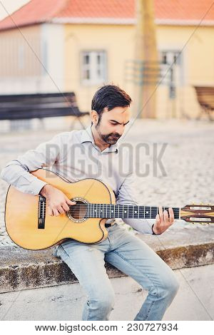 A Cute Stylish Man With A Beard Sits On A Concrete Curb In The Street And Plays An Acoustic Guitar A