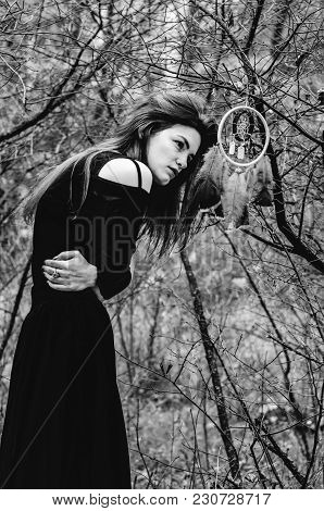 Young Witch In Black Dress Is Making Magic Witchcraft In The Forest With A Dreamcatcher