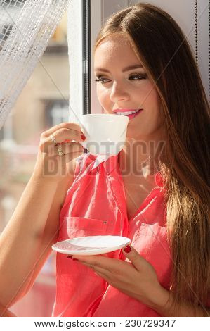 Young Woman Sitting On Windowsill Looking Through Window Enjoying Her Free Time, Relaxing While Drin