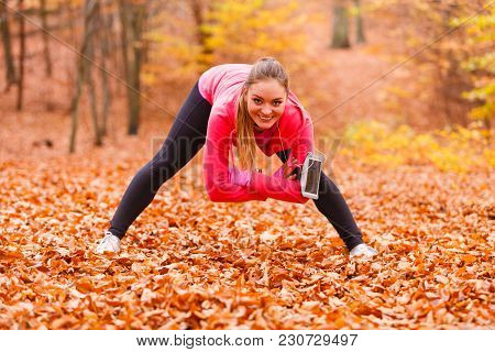 Stretching And Exercising. Young Sporty Fit Girl Doing Sports Outdoor. Positive Woman Spending Time