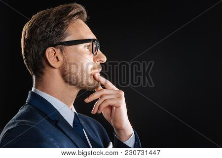 Think About It. Deep Busy Bespectacled Man Being In The Dark Room Touching To His Chin And Thinking.