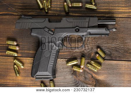 The Pistol On The Gate Delay, Surrounded By Cartridges On A Wooden Table