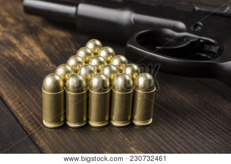 Cartridges Lined With A Pyramid With A Gun On A Wooden Table