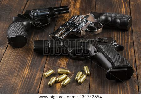Two Revolvers, One Pistol With Cartridges On A Wooden Table