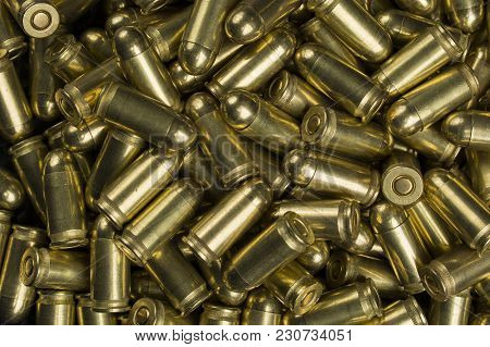 Scattered Cartridges Of The Ninth Caliber On A Wooden Table
