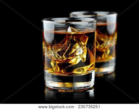 Glasses Of Whiskey With Ice Isolated On Black Background With Reflection. Close Up View. Selective F