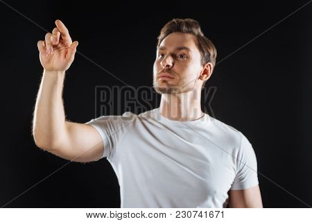 Lets Try. Concentrated Calm Handsome Man Standing In The Spacious Room Holding Hand Up And Pointing