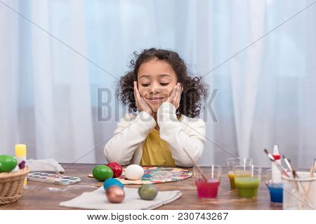 African American Kid Resting Chin On Hands And Looking At Painted Easter Eggs