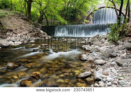 Traditional Stone Bridge And Waterfalls Near Paleokaria Village In Thessaly, Greece