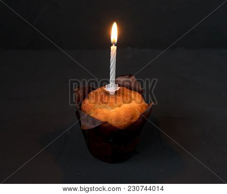 A Cake With A Candle On A Black Background. The Candle Of Mourning Is Burning.