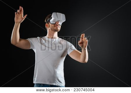 Good Feeling. Stylish Occupied Beardful Man Holding Hands Up Smiling And Examining Vr Glasses.