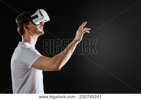 Try To Touch. Occupied Impressed Unshaken Man Looking Up Through The Vr Glasses Being In The Spaciou