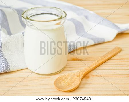 A Jar Of Plain Yogurt On Wooden Table. Healthy Food Concept.