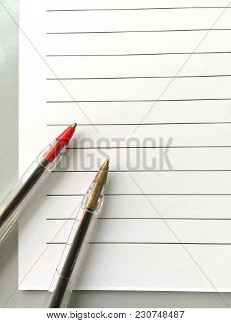 Two Ballpoint Pens On A Blank Sheet Of Notebook