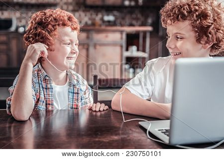 Modern Entertainment. Positive Happy Nice Boys Sitting In Front Of The Laptop And Wearing Headphones