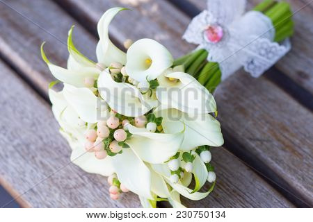Elegant Bridal Bouquet Of White Calla Lilies, Boutonniere On The Table