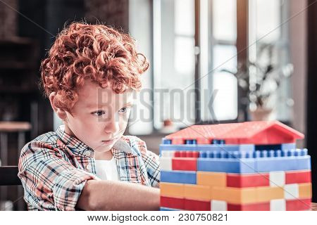 Young Architect. Nice Pleasant Smart Boy Using A Constructor Set And Building A House While Entertai