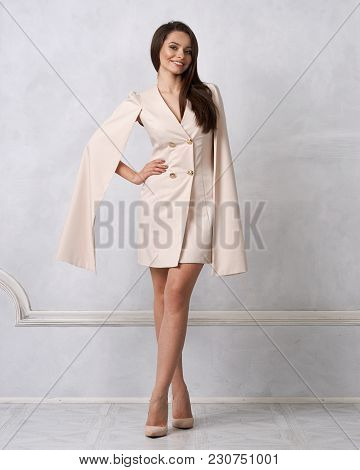 Attractive Brunette Female Model Wearing Mini Beige Dress With Golden Buttons, Split, Long Hanging S