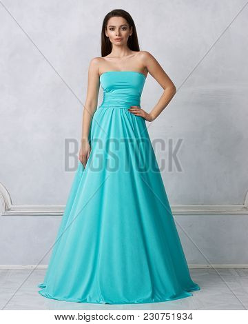 Beautiful Long Haired Young Woman Dressed In Stylish Turquoise Blue Bandeau Maxi Dress Posing Agains