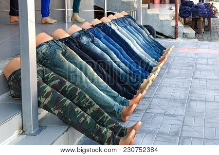 Mannequins In The Form Of Legs, Dressed In Jeans Lie, Laid Out At Srairs In Line. Concept Of  Alike,