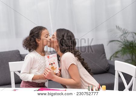 African American Mother Kissing Daughter For Greeting Card On Mothers Day