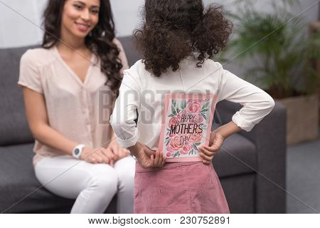 Rear View Of African American Daughter Presenting Greeting Card To Mother On Mothers Day