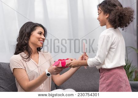 Side View Of African American Daughter Presenting Gifts To Mother On Mothers Day