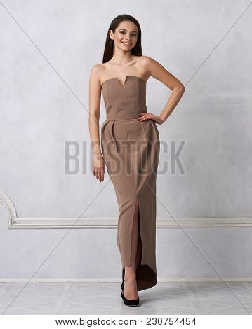 Beautiful Brunette Female Model Dressed In Strapless Taupe Brown Formal Dress Posing In Studio. Attr