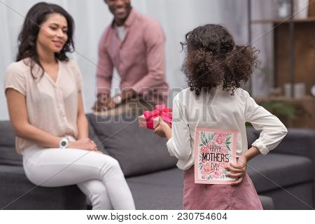 Rear View Of African American Daughter Presenting Gifts To Mother On Mothers Day