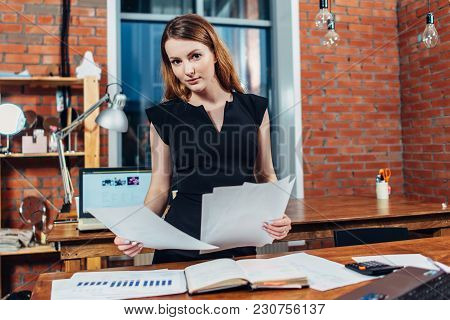Serious Woman Reading Papers Studying Resumes Standing At Work Desk In Stylish Office.