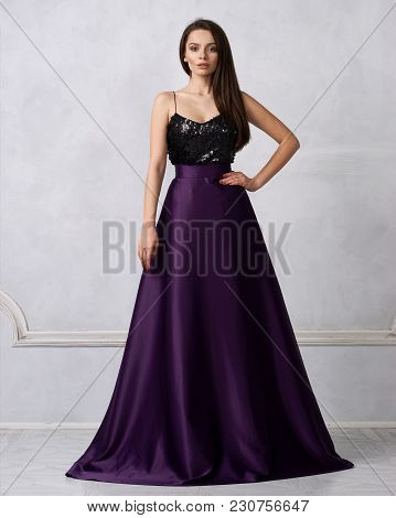 Charming Brunette Woman Dressed In Formal Maxi Dress With Top Decorated With Black Sequins And Purpl