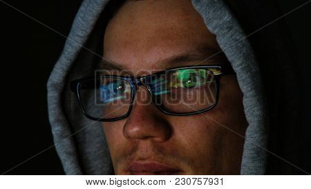 Hacker In Glasses And A Hood Works Behind A Computer In The Dark, The Program Code Is Reflected In G