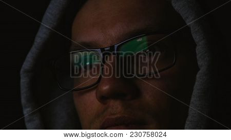 Programmer With Glasses And A Hood Works At A Computer In The Dark, A Reflection In Glasses Close-up