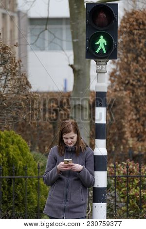 Young Woman Waits At A Traffic Light That Is On Green But Does Not Pay Attention To The Traffic Beca