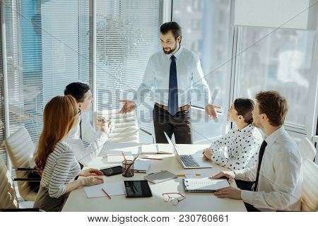Important Issues. Handsome Young Boss Standing At The Head Of The Table And Talking To His Colleague